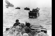 Canadian troops in landing crafts approach a stretch of coa