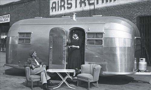 Wally Byam, the founder of Airstream, seated beside an Airs