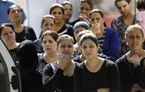 raqi women watch as the coffins of two slain priests are ca