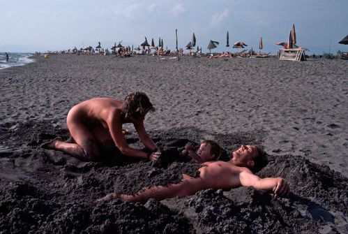 Happy Family Nudism Playing And Relaxing In Beach