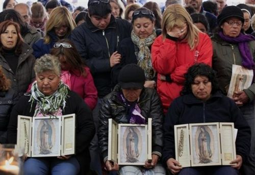 Relatives of trapped miners hold images of the Virgin of Gu