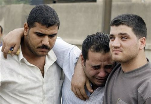 An Iraqi man is consoled by friends