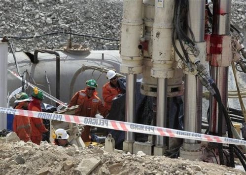 Men work on a new drill to be used in the rescue operation