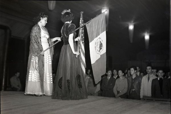 Two-women-holding-Mexican-and-American-flags-with-audience-jpg