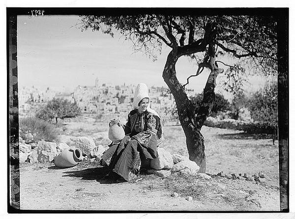 Bethlehem woman with jar seated under almond tree. Bethlehem in background, between 1934 and 1939