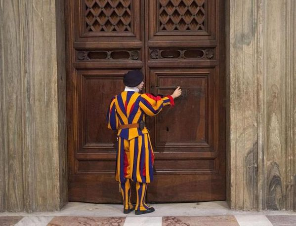 617538-a-member-of-the-swiss-guard-unlocks-a-door-to-the-si.jpg