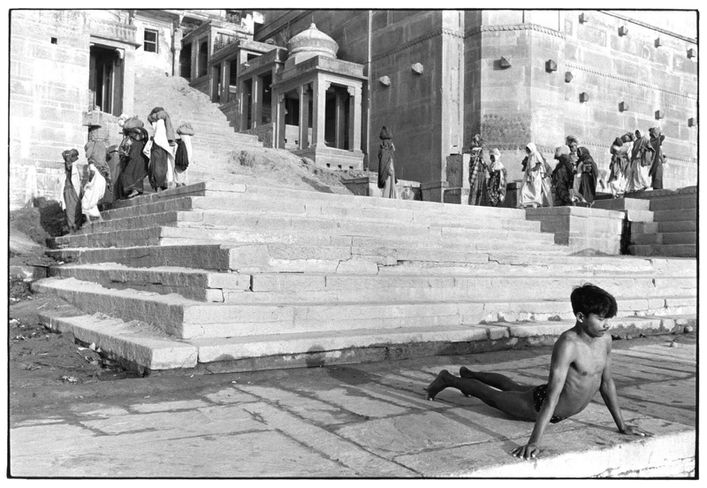 Man-performing-yoga-at-base-of-steps-on-ghat--women-in-back.jpg