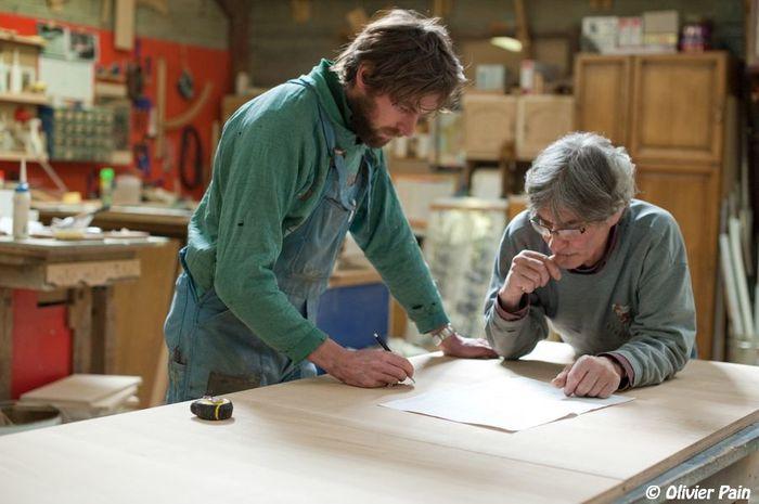 Employés regardant le plan d'un nouveau meuble